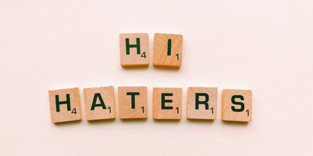 Scrabble tiles that spell out hi haters